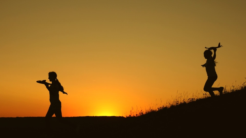 Children run from mountain with an airplane in hand against backdrop of sun. Dreams of flying. Happy childhood concept. girls play with toy plane at sunset. Silhouette of children playing on plane | Shutterstock HD Video #1049992549
