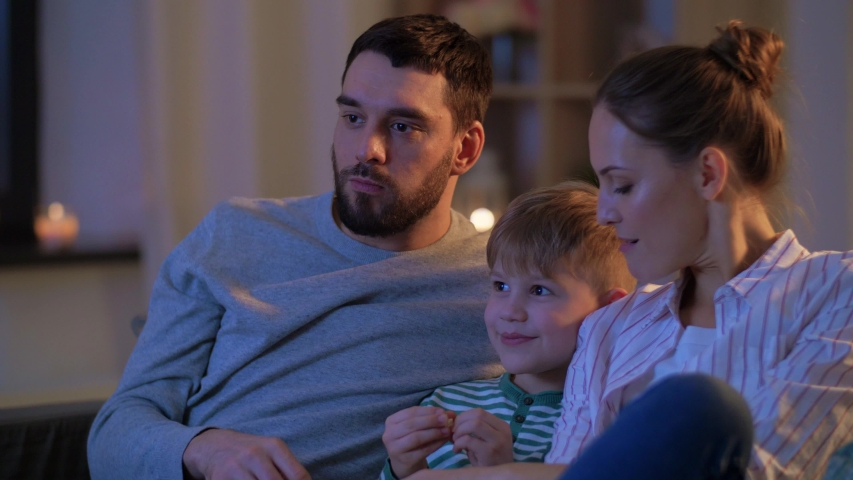 Family, leisure and people concept - happy smiling father, mother and little son eating popcorn and watching tv at home in evening | Shutterstock HD Video #1050019729