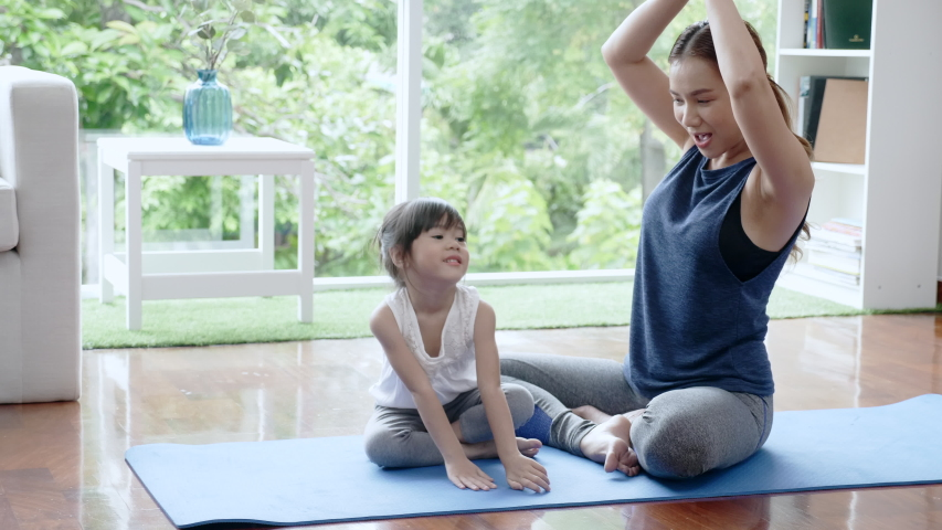Asian family Mother is teaching her daughter to do yoga at home. Practice your physical workout skills to be strong and to concentrate. Holiday activities that make many families happy | Shutterstock HD Video #1050043819