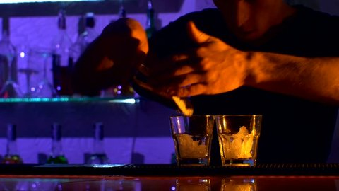 Bartender, barman is making delicious cocktail at bar counter using ice and sweet liquor, and making tricks, shots