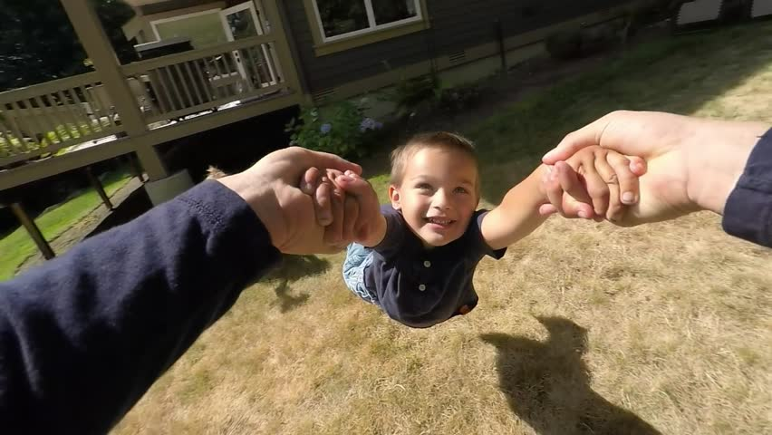 Point of view footage of a young boy being spun around by his arms, by his father.