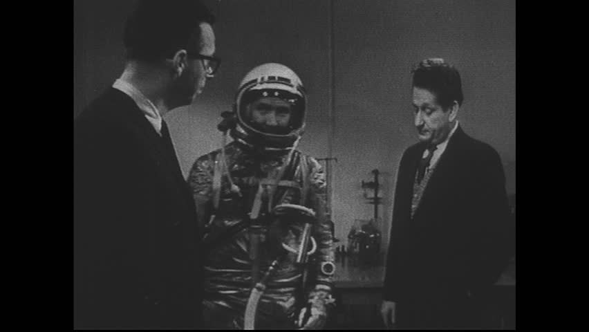UNITED STATES 1960s: Two men on set, model wearing space suit exits, new model enters / Close up of man in suit, tilt down suit.