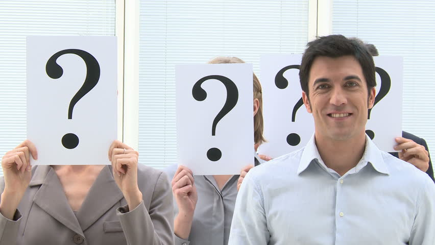 Happy smiling business man standing out of the crowd with other people hiding their face behind a question mark sign. Happy smiling businessman stands out from the crowd.