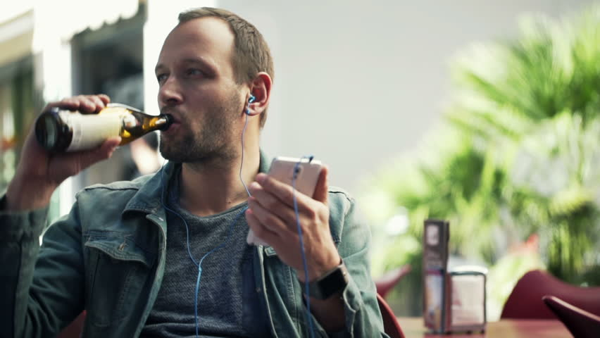 Young man in earphones listen to the music, drink beer in cafe