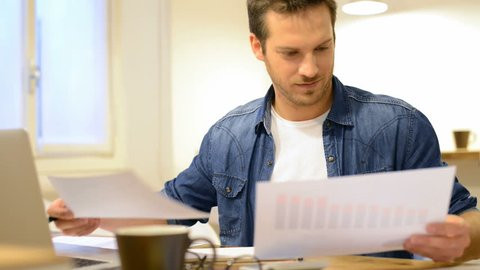 Happy young businessman reading paperwork at desk in office. Casual man smiling at work. Young man working at business document and checking the file on his laptop. Man working at documents.