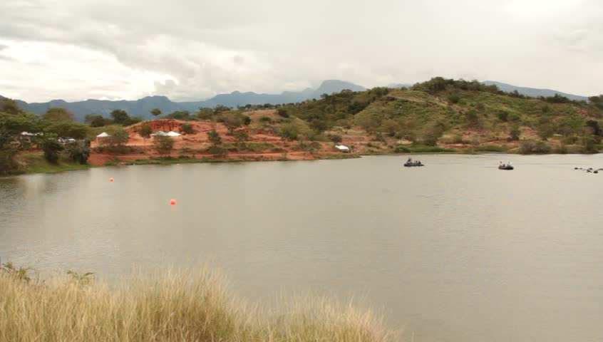 Pan Shot of Mountain Lake and Rafts in Distance