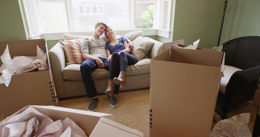 Tired happy couple sitting on couch after unpacking | Shutterstock HD Video #10594409