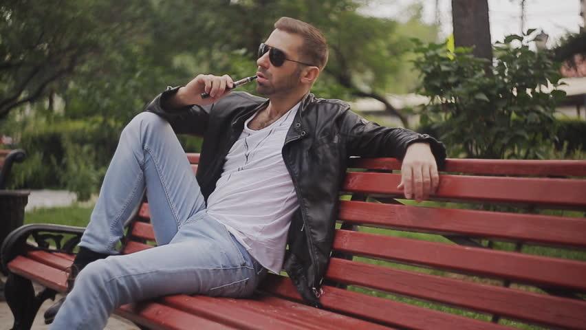 a man on a bench smoking electronic cigarette