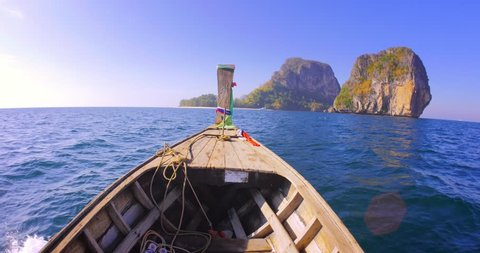 Adventure background. Marine landscape with wooden fishing boat going to distant rocky island at early sunset near Phuket in Thailand