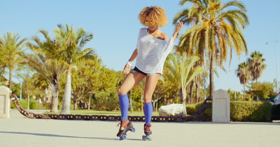 Beautiful And Sexy Girl Dancing on Roller Skates at Tropical Park in Slow Motion Video