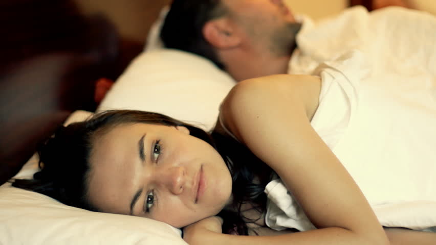 Unhappy woman lying in bed, man in the background