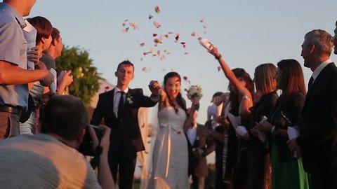 Reggio Emilia, Italy 29/07/2014. Friends congratulate the just married. Guests sprinkled on the bride and groom rose petals. Wedding ceremony.