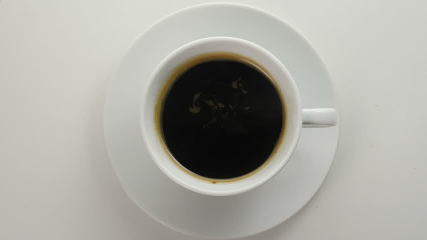 White cup with a black coffee. 4k footage. Black, steaming coffee in white cup. Close up. Top view.