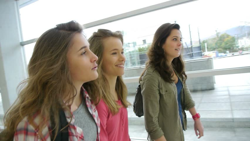 Teenage girls walking in high-school hall