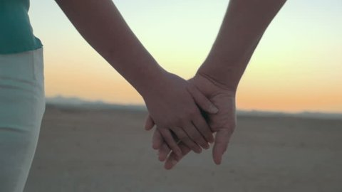 Slow motion close-up shot of man and woman taking hands on background of evening sky. Symbol of love and devotion