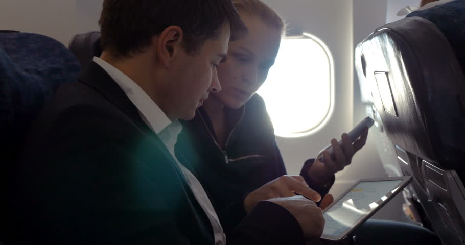 Young man and woman in the plane. They discussing some business matters using tablet computer and making agreement with handshake