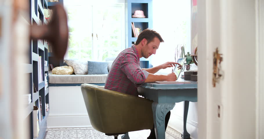 view through door showing man working in home office 4k stock video clip