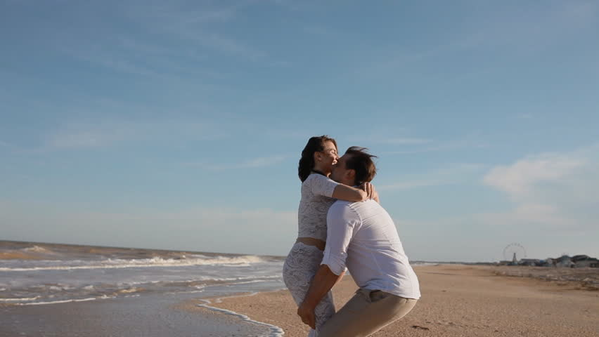 Young man take his woman on his hands and circling.View on the beach in summer time. | Shutterstock HD Video #10698929
