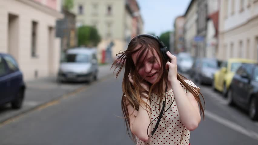 Pretty young girl listening music in headphones on a deserted street.