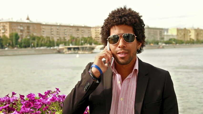 Men talking in sunglasses on the phone and smiling | Shutterstock HD Video #10705019