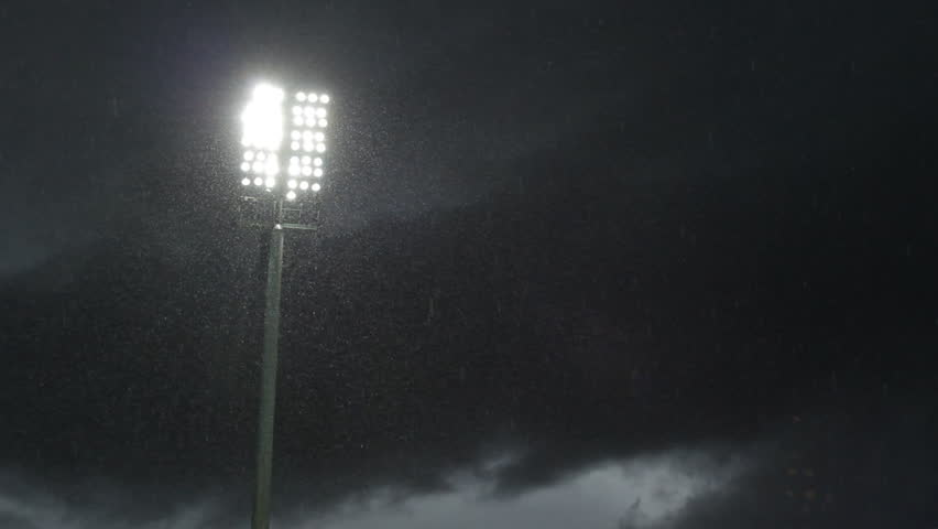Lightning stadium lights stand in the late evening, raining weather with black clouds
