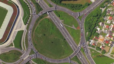 AERIAL: Flying above huge roundabout full of cars and trucks at rush hour