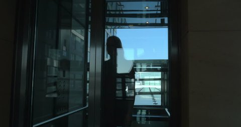 Steadicam shot of young woman with trolley bag walking out the hotel elevator and passing the hall.