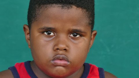 Portrait of sad children with emotions and feelings. Worried hispanic or black young boy looking at camera, overweight male child with depressed expression on face. Close-up, copy space