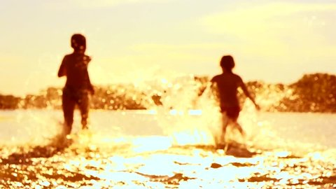 Kids having fun in water outdoors. Happy Children joyful little boy and girl playing in River Water. Summer fun. Slow motion video footage 1080p. Slowmo, high speed camera