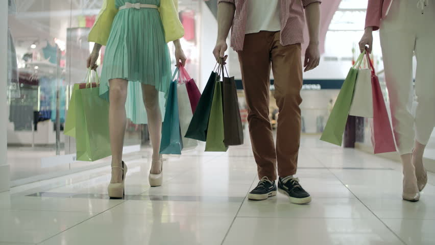 Low section of three unidentified people with shopping bags approaching camera | Shutterstock HD Video #10762649