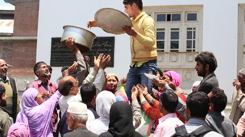 SRINAGAR, INDIA - JUNE 11, 2015: Unknown Indian man feeds the hungry people near a Muslim mosque. Kashmiris are fighting for their freedom for 20 years now. Kashmir became dangerous again.