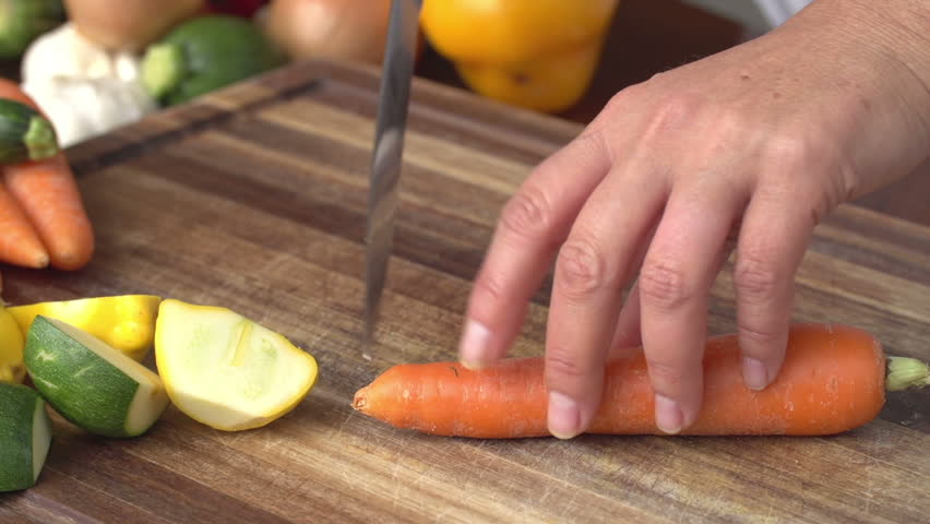 Chef cutting carrot with vegetables in the background,South Africa | Shutterstock HD Video #10797269