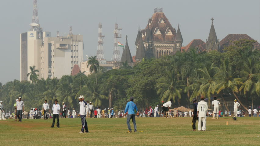 MUMBAI, INDIA - 2 NOVEMBER 2014: Young men play cricket in front of the Bombay University and a large Tata office tower, perhaps symbolizing the old and new India.