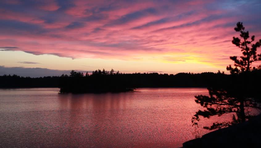 Wonderful pink sunset on forest lake, Karelia, Russia