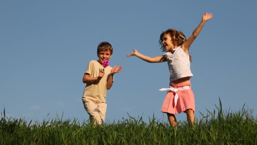 boy shakes rattle in form of colored hands, and his little sister dances cheerfully bouncing against blue sky