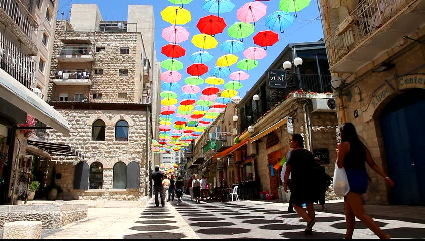 JERUSALEM,ISRAEL - JULY 19,2015:Colorful umbrellas floating magically in the sunny blue sky above pedestrians flocking cobblestone-lined streets.Whimsical,cheery fashion installation.Street decoration