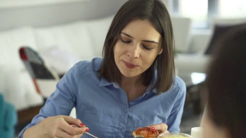 Young woman talking and eating scrambled eggs sitting by table at home
