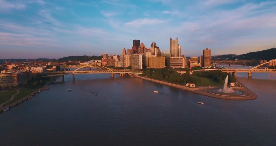 An aerial tracking shot of Pittsburgh, Pennsylvania and Point State Park at sunset.  (Pittsburgh PA, July 2015)