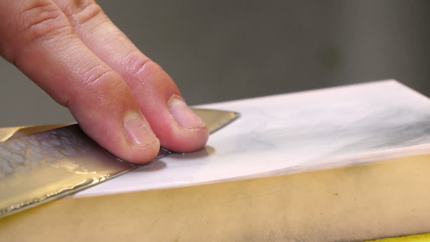 Sushi Chef Sharpening his Knife Blade with a Pink Stone. Professional chef with kitchen knives. A sushi-man wets and sharpens his Japanese knife. Preparing sashimi knife blade.