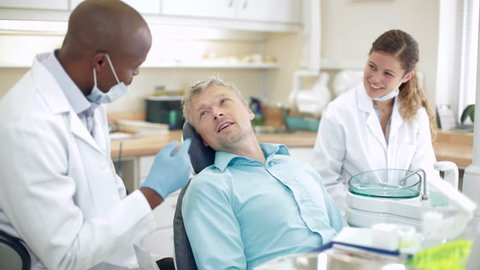 Scene in dentist office where dentist discusses treatment with smiling male patient who seems relaxed and happy. The smiling dental nurse looks on.