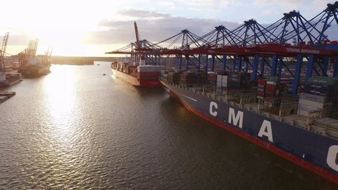 Hamburg, 8 June 2015 - Flight over Hamburg container port with ships and cranes at sunset