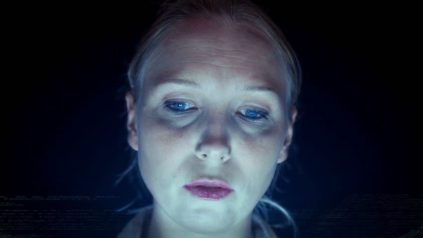 Young woman looking at holographic display below her face lit from bottom 4K | Shutterstock HD Video #11003129