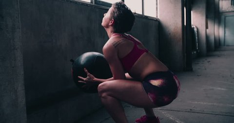 Young woman doing crossfit training ball slams against a concrete wall with a medicine ball