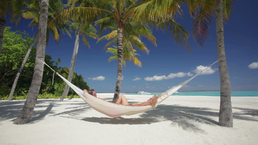young man with girlfriend relaxing in hammock at tropical beach with palm trees
