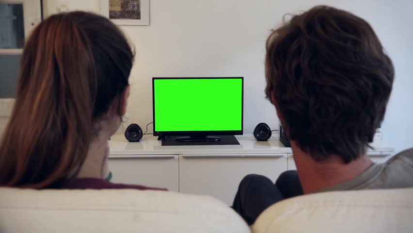 Green Screen TV Couple - Full HD. PARIS, FRANCE - 28 JULY 2015; Couple watches television with green screen in living room / shot behind model's  | Shutterstock HD Video #11020250