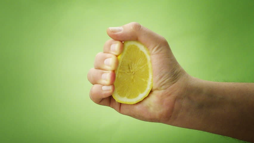 hand squeezing lemon on green background - 1080p