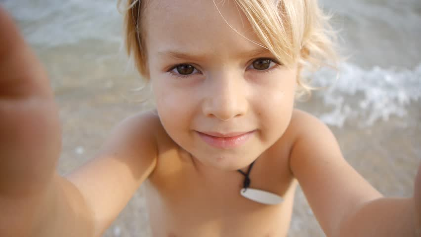 A cute little child video chats on smart phone on the beach on blue sea background. Using a portable handheld device on summer vacation. Talking on a mobile. Doing selfie. Wide angle view | Shutterstock HD Video #11046518