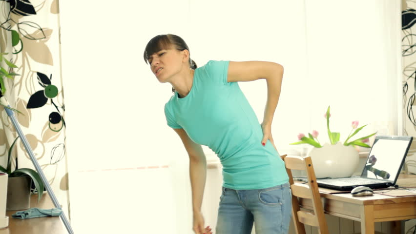 Woman having back pain while cleaning floor with mop