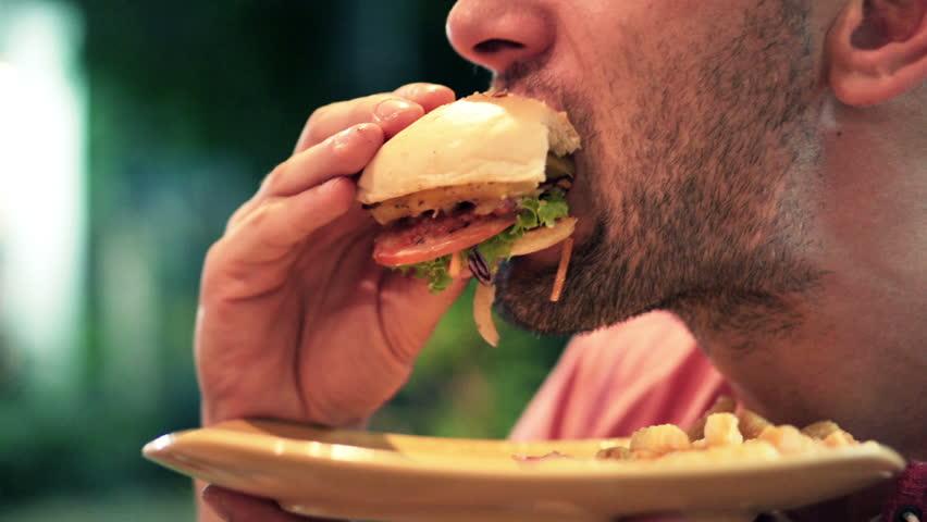Young man eating fast food, hamburger in city at night