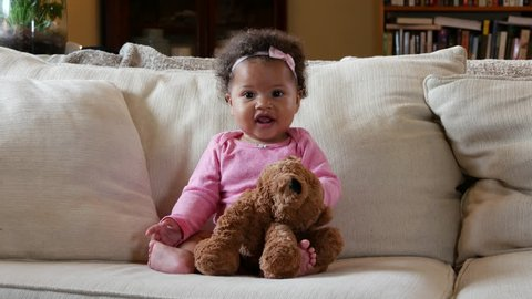 Happy baby girl with teddy bear smiles and laughs